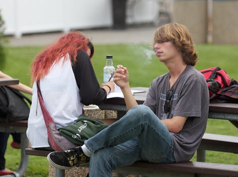 <b>A DRAG:</b>  Casey Mokicky (right) smokes a cigarette while his friend Valerie Martin does homework at a designated smoking area on City College's West Campus. The Board of Trustees voted to eliminate the three current smoking areas, making the campus completely smoke-free by August 5.