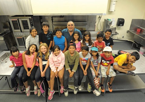 <b>YOUNG CHEFS:</b>  City Outreach Supervisor Mark Alvarado poses in front of the Westside Neighborhood Center's commercial kitchen with Summer Fun kids.