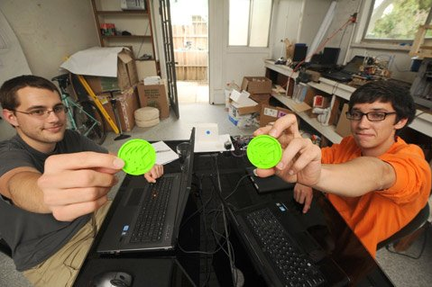 Mechanical engineering interns Chris Marzano (left) and Alex Herpy hold up 3D printed objects.