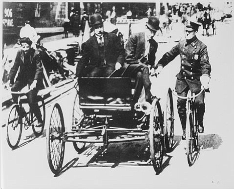 An early officer on bike makes a traffic stop.