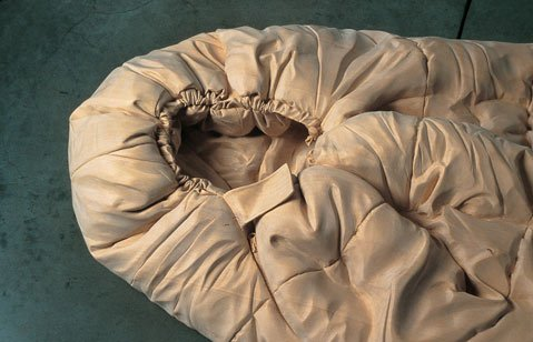 "<b>BOARD BAG:</b>  This life-sized sculpture of a sleeping bag is called ""Sleeping Range"" and was hand-carved out of wood by Los Angeles artist Ricky Swallow in 2002."