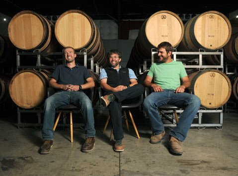 """<b>TALKIN' 'BOUT THE GHETTO:</b> The collaborative, workshop-like atmosphere of the Lompoc Wine Ghetto is what has allowed Sashi Moorman (middle) to take on multiple projects under his own winemaking business, Provignage, which employs winemaker John Faulkner (left) and partners with vineyard expert Chris King (right) of Cosecha Farming. """"Without this place,"""" said Moorman, """"I wouldn't be able to do what I'm doing now."""""""