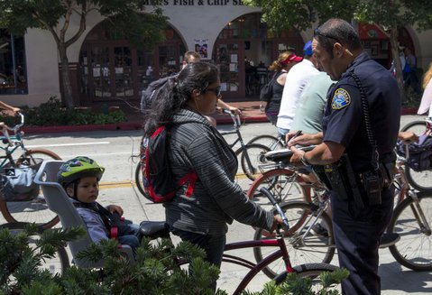 <b>NO PUN INTENDED:</b>  Officer John Bacon writes Patricia Marquez a ticket for allegedly running a red light on her bicycle at the State and Haley streets intersection during the August 4 Fiesta Cruiser Run.
