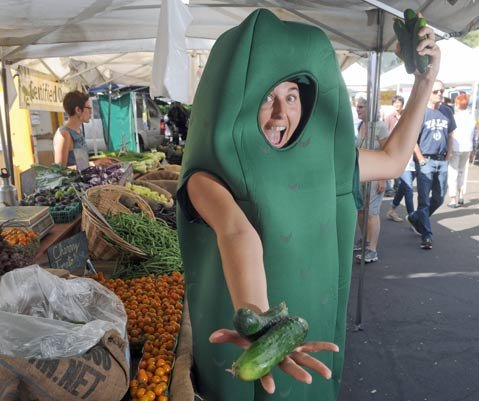 Katie Flabo in a pickle costume at Fairview Garden's stand at Farmers Market supporting the upcomming Fermentation festival.