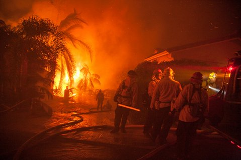 Tea Fire. Firefighters close to being overrun by flames from a home burring below them.