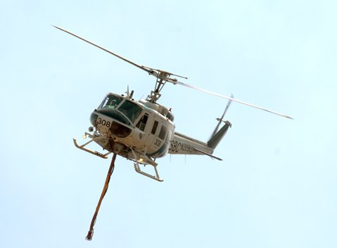 <b>PRICEY FIX:</b>  Sheriff's Helicopter 308, seen here fighting the Lookout Fire on October 17, 2012, went way over its expected repair costs.