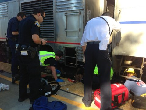 Emergency responders work to free the trapped bicyclist