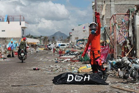 A member of the Philippine Bureau of Fire Protection in a heavy gas mask stands over a body bag and gestures to alert his colleagues in the garbage truck used to transport victims' remains to a mass grave.