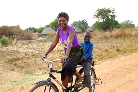 A Zambian health-care worker uses her bike to transport her family when she's not visiting patients.