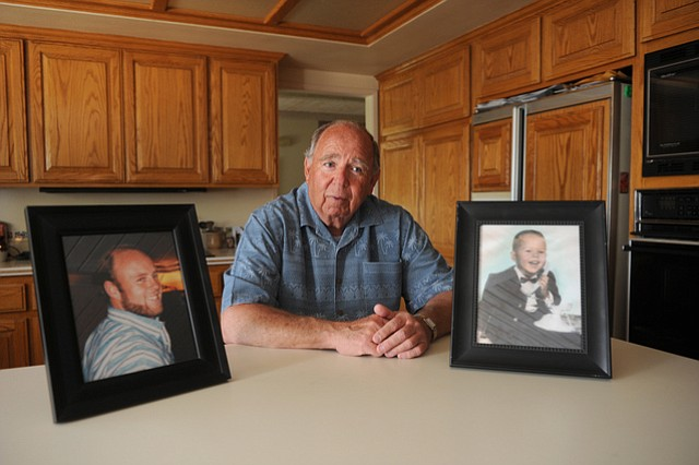 Richard Detty sits with photos of his son, Clifford