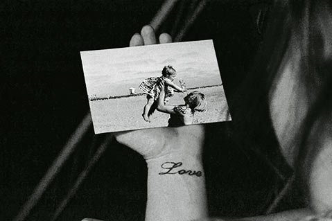 """In Lance Corporal Jennifer Ratliff's self-portrait """"Stella Jo,"""" she holds a photo of her best friend and her daughter, whom Ratliff cared for while her friend deployed. Ratliff had been injured in Iraq while serving as a machine gunner. The image """"speaks volumes regarding Marines' love of family and comrades,"""" says the author."""
