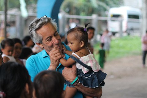 <b>NURTURED IN NATURE:</b> Howard Schiffer holds aloft a child during an information meeting and vitamin distribution in Javier, Leyte.