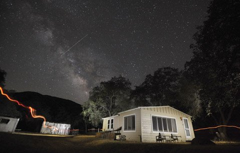 A 30 second exposure on a clear summer night in Cuyama Valley shows off the Milky Way, a meteor passing by, and a cabin illuminated with a small flashlight