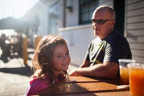 Alex Hoskins waits for a burger at On the Alley at the harbor with her dad, Mark Hoskins.