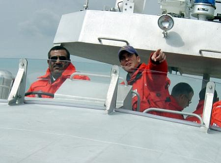 Officer Terrell Horne points the way as Lt. Col. Rasheed Mansoor R. M. Al-Borashid of Qatar's Coast and Borders Security Department steers a Motor Lifeboat through Charleston Harbor