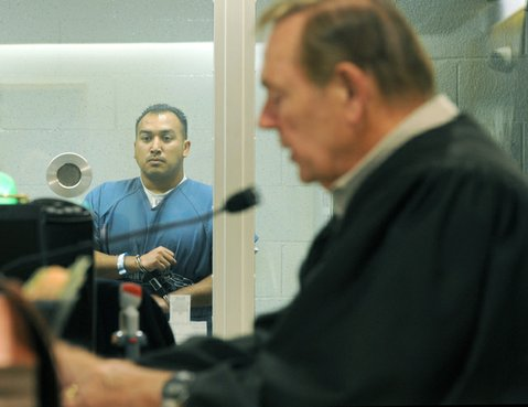 Raymond Morua stands behind the a glass partition as Judge Thomas Adams deliberates