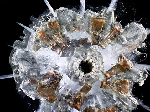 "<b>HIGH IMPACT:</b> In ""9mm Automatic,"" Deborah Bay captures the jewel-like shine of shrapnel embedded in Plexiglas."