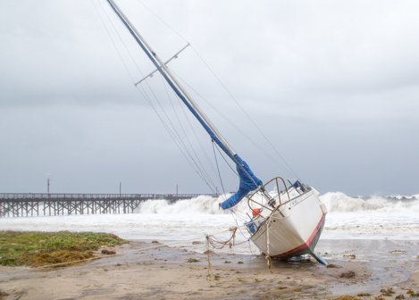 Sailboat beached in front of the Beachside Bar Cafe while surf pounds the Goleta pier.
