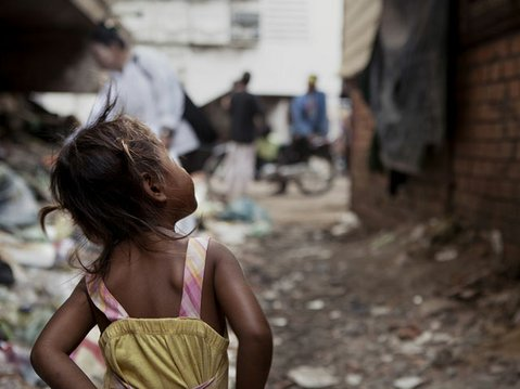 An unsupervised three year old girl roams near the swelling trash piles that line her home.