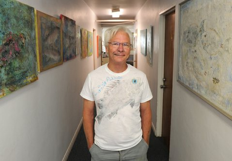 Craig Rudholm flanked by his fish prints at New House.