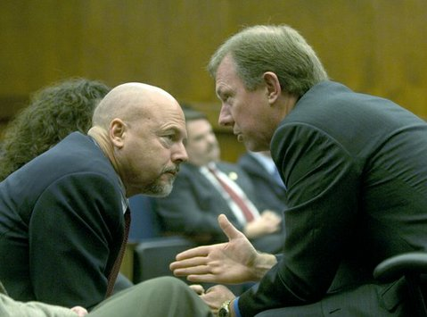 Grady Williams (left) speaks with Office of Emergency Management chief Michael Harris at a County Board of Supervisors meeting in January 2010