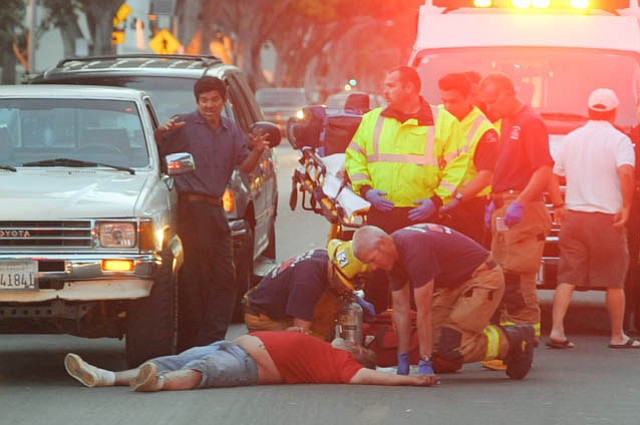 A man is treated after an assault near the intersection of Mason and Milpas streets while a witness (left) describes the attack (May 17, 2014)