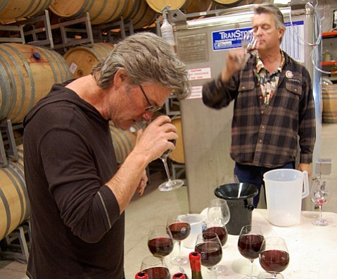 <b>CELEB SIPPER:</b> Kurt Russell sniffs his way toward a 2012 blend of pinot noir for his Gogi project at the Ampelos Cellars facility in Lompoc, where owner/winemaker Peter Work (right) advises the actor.