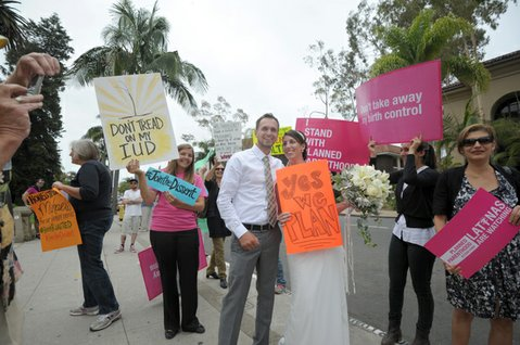 After taking vows at the Santa Barbara Courthouse Jake and Andy Berban pick u a sign during the Hobby Lobby protest.