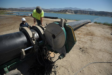 <b>LONG STRAW:</b> W. J. Whorf seals sections of new pipe to reach and pump from deeper points of Lake Cachuma.