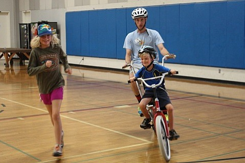 Sydney and Channing Long (right) race around the gym.