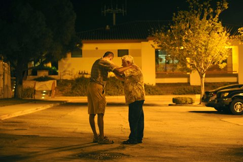 <b>GOOD-BYE PRAYER: </b> Just-released inmate D.J. (left) shares a moment with Light Brigade volunteer Maeton Freel before Freel leaves for the night.