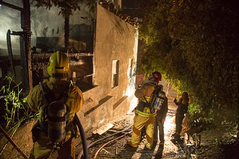 Fireman interviews what appears to be either the owners or residents of a home in the 3900 block of Calle Cita in the North La Cumbre area.
