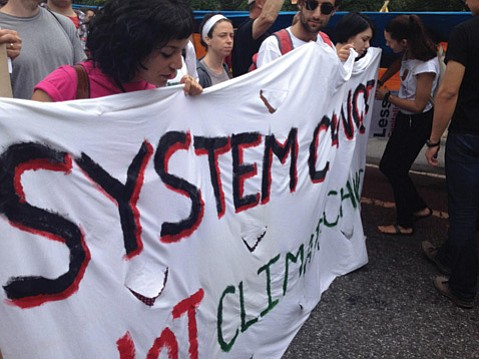 UCSB Sociology grads Christina Awadallah and Zach Rosenberg hold a banner at the Manhattan protest.