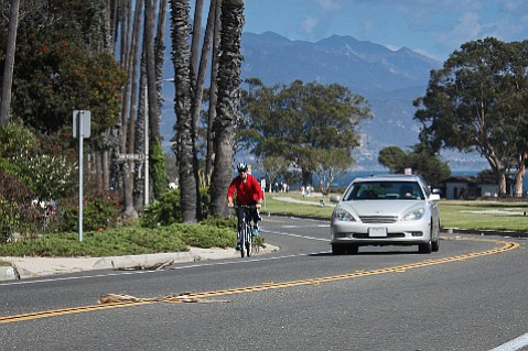 A cyclist and motorist move safely along Santa Barbara's Shoreline Drive.