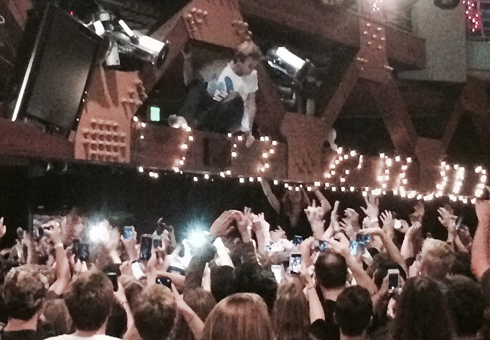 Fans cheer on Mac DeMarco at his show at UCSB Friday night moments before he was detained on stage for crowd surfing and hanging in the venue's ceiling beams.