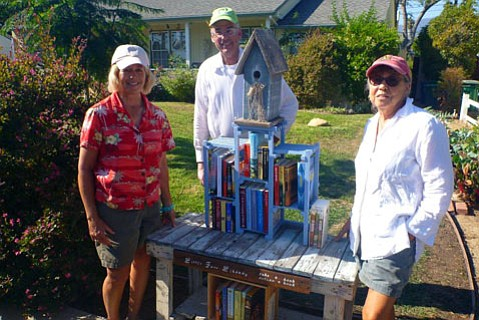 <b>FREE READS:</b>  The little library set up by Sue De Lapa (left), Peter De Lapa, and Sandy Cornett soon had more books added.