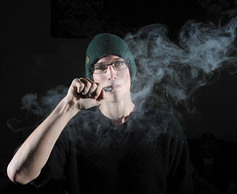 <b>THROUGH THE HAZE:</b>  Collin Walker at Santa Barbara Vapor puffs away at his e-cigarette.