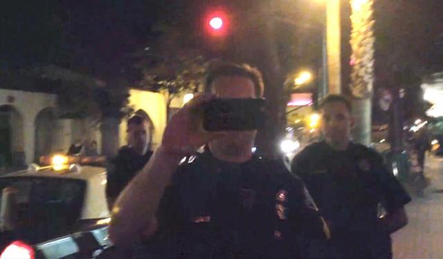 DUELING SMARTPHONES: Sgt. Eric Beecher films a bystander taking video of an arrest on State Street