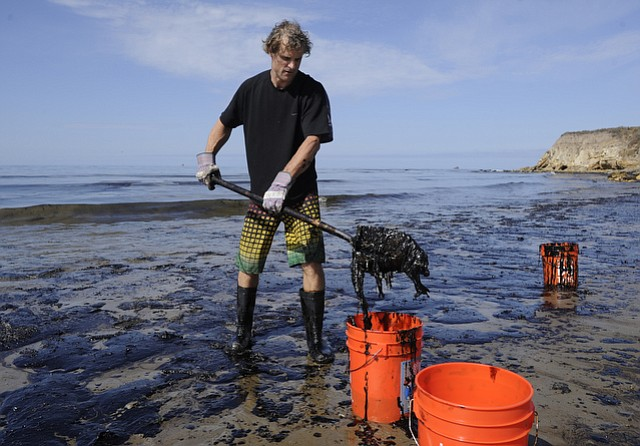 """<b>IN THE THICK OF IT:</b>  Gaviota resident Josh fills bucket after bucket with oil. He and others said they've found pockets of crude east of the spill as the wind and the waves push the slick further down the coast.""""We need to hold the line,"""" he said. Citing health concerns, officials are asking would-be volunteers to steer clear of the beaches and to call (877) 823-6926 if they spot any oiled animals."""