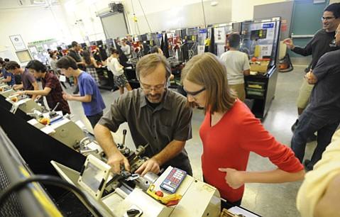 Adams Elementary teacher Sean Federbusch helps DPEA student Emma Schott with machinery operation and safety.