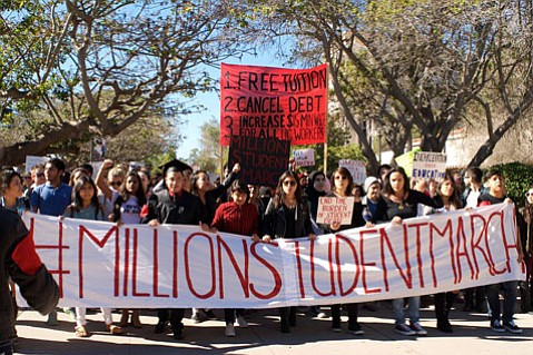 UCSB student protestors carry a #MillionStudentMarch banner and signs stating their demands.