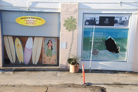 A broken window at Surf 'N' Wear's Beach House