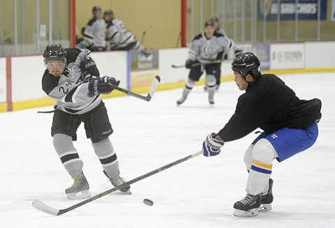<strong>GOOD LAND GOALS:</strong> Eric Valois (left) of the Santa Barbara Kings fires the puck past a UCSB defender during Adult Hockey League action at Ice in Paradise.