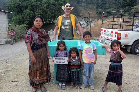 <strong>TRAVEL MILES TO GIVE SMILES:</strong> Rotarian Steve Petersen presents a washing basin to a happy Guatemalan family.