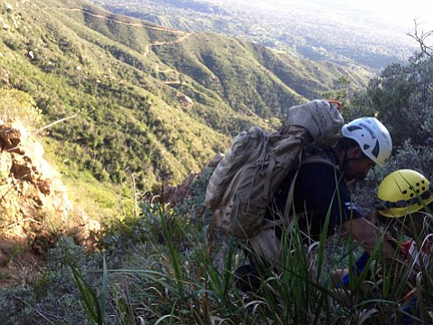 A Search and Rescue volunteer secures the City College student to bring him back up to the trail.