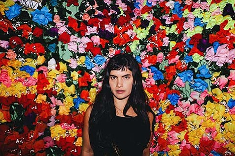 <b>ALL AROUND US:</b>  Seattle's Briana Marela, surrounded by flowers, helps bring tidings of spring to the Dashain Haus at tonight's vegan potluck concert.