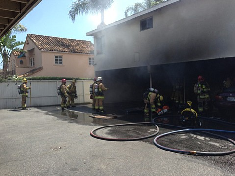 Firefighters beat back a carport fire Monday afternoon at a downtown apartment complex.