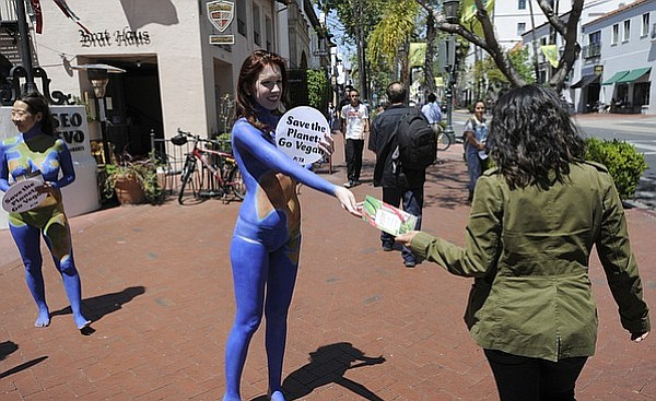 Her body painted in blue oceans, Meggan Anderson hands out PETA literature downtown as part of a national campaign to go vegan for Earth Day.