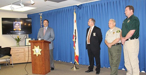 Murder suspect Larry Lee is pictured on the screen behind Sheriff Bill Brown during the press conference announcing a lead in the 1988 death of Vernon Kendrick.