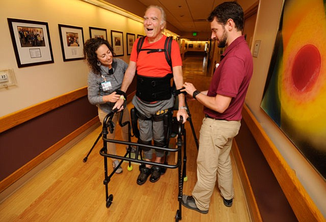Bertrand de Gabriac is helped by Amber Gonzalez and Noah Gaines, both Doctors of Physical Therapy, during a session using the Ekso exoskeleton robotic legs at Cottage Rehabilitation Hospital.